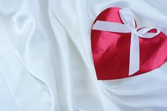 Red heart  on white satin Stock Photos