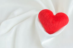 Red heart on white satin textile background Royalty Free Stock Photography