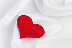 Red heart on white silk Royalty Free Stock Images