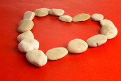 Red heart with white stones. Red paper heart and small pebbles of white river Stock Image