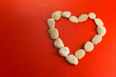 Red heart with white stones. Red paper heart and small pebbles of white river Stock Photo