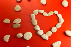 Red heart with white stones. Red paper heart and small pebbles of white river Stock Images