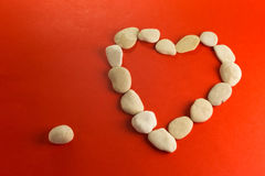 Red heart with white stones. Red paper heart and small pebbles of white river Stock Photos
