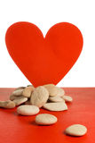 Red heart with white stones. Red paper heart and small pebbles of white river Royalty Free Stock Photo