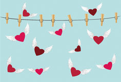 Red heart with wings flying around the rope with clothespins. Stock Photos