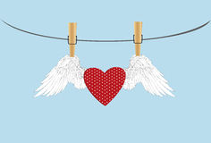 Red heart with wings hanging on a rope. clothes pegs Stock Photos