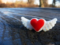 Red heart with wings magnet on picnic table. Red heart with wings glass magnet on textured, wooden picnic table Royalty Free Stock Images