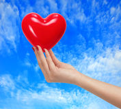 Red heart in woman hand over blue sky Royalty Free Stock Photography