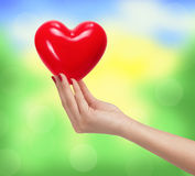 Red heart in woman hand over bright blurred nature background Royalty Free Stock Image