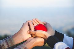 Red heart in woman and man hands, hands holding a soft heart shape, Couple love, Valentine`s Day stock image