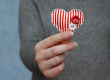 Red heart in woman's hand on blue background Stock Image