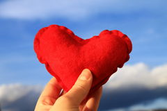 Red heart in woman's hand with blue sky in background , Valentine's day Stock Photography