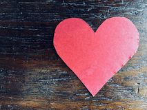 Red heart on wood background. Red paper heart on a dark wooden background royalty free stock photography
