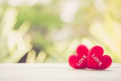 Red heart on wood table top with nature blur bokeh background. Valentines day concept Stock Photos