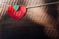 Red heart on wooden background with light shadow. Royalty Free Stock Photos