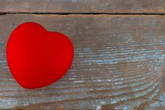 A red heart on the wooden background.  Stock Photo