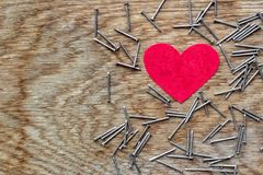 Red heart on wooden background surrounded by iron nails with copy space. Red love heart on wooden background surrounded by iron nails royalty free stock photo