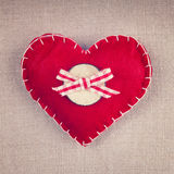 Red heart with wooden button and bow on vintage fabric Stock Photo