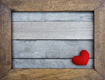 Red heart in wooden frame on wood background Stock Photos