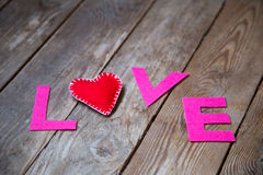 Red heart and word  love. Red heart and love on the wooden background Royalty Free Stock Image