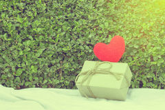 Red heart yarn and gift box. Red heart yarn and gift box on white fabric. Tree leaf bushes green fence, Texture background Royalty Free Stock Photos