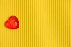 Red heart on yellow background on left side, sign of love and romance, greeting card for womens day or valentine. Red plastic heart on yellow corrugated stock photos