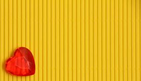 Red heart on yellow background with vertical pattern, sign of love and romance, greeting card for womens day or valentine. Red plastic heart on yellow corrugated stock image