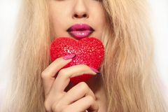 Red heart. Young beautiful girl with blond hair holding a heart symbol red color Stock Photography