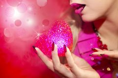 Red heart. Young beautiful girl with blond hair holding a heart symbol red color Stock Photo