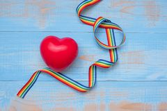 Red heartr shape with LGBTQ Rainbow ribbon on blue pastel wooden background for Lesbian, Gay, Bisexual, Transgender and Queer. Community stock photography