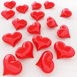 Red hearts. Red shiny hearts on the white plane Stock Image