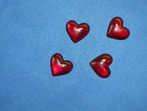 Red hearts. Four red hearts isolated on blue fabric Royalty Free Stock Photo
