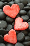 Red hearts. Three red herts on a black stones Royalty Free Stock Photography