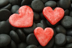 Red hearts. Three red herts on a black stones Royalty Free Stock Photos