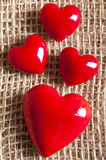 Red hearts. Four red hearts over sacking background Stock Images