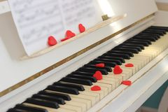 Red hearts adorn piano keys. Valentine`s Day . Red hearts adorn piano keys Stock Photography