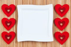 Red hearts on a background of wood, white square plate a card for Valentine`s Day. With some free space for your text or sign. Valentines day Stock Photo