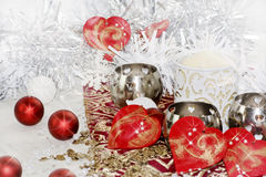Red hearts and baubles on Christmas table. A Christmas funny reindeer decoration on table with red hearts Royalty Free Stock Photography