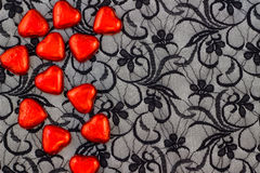 Red hearts on black lace Stock Photography