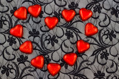 Red hearts on black lace Stock Photos