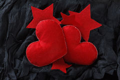 Red hearts on black paper background. Love concept, red hearts and stars on black paper texture. Dark background with two felt hearts for use in graphic design Stock Photography