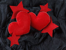 Red hearts on black paper background. Love concept, red hearts and stars on black paper texture. Dark background with two felt hearts for use in graphic design Stock Photos