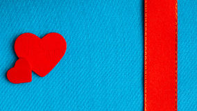 Red hearts on blue cloth background. Royalty Free Stock Photos