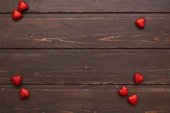 Red hearts on a brown wooden background. Valentine's Day Stock Photo