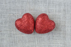 Red Hearts on Burlap Background Stock Images