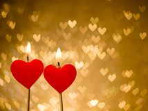 Red hearts candles on golden hearts bokeh as background Stock Photography