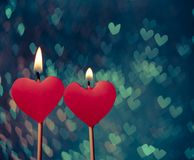 Red hearts candles on vintage hearts bokeh as background Royalty Free Stock Image