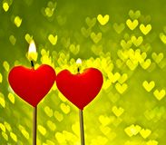 Red hearts candles on yellow hearts bokeh as background Stock Image