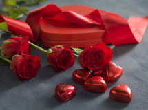 Red hearts chocolates in front of red roses and hart shaped box royalty free stock photo