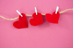 Red hearts with cloth peg hanging on rope. Against pink background Stock Photo